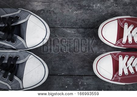 Two pairs of well-worn sneakers on a wooden surface top view