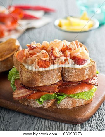 A delicious lobster club sandwich with bacon lettuce tomato and mayonnaise on toasted bread.