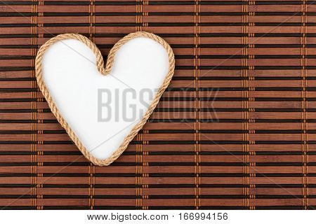 Rope in the shape of a heart with a place for your text lying on a bamboo mat. View from above