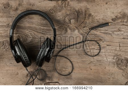 Headphones lies on wooden desk table. Music concept. Top view with copy space
