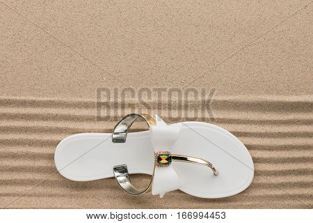 Trendy white flip flops decorated with rhinestones standing on the beach sand. View from above