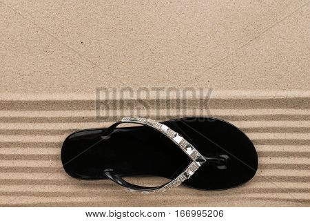 Trendy black flip flops decorated with rhinestones standing on the beach sand. View from above
