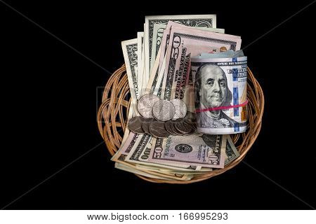 Basket with US dollars and coins isolated on black