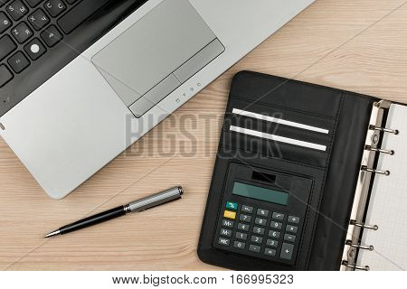 Laptop with diary and pen on wooden table. Overhead view of working desk.