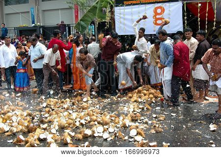 Georgetown Penang Malaysia - 7 February 2009: Devotees smashing coconuts on the ground to greet the impending arrival of the god Murugan.