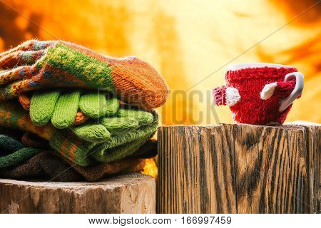 Wool hat, scarf, socks and gloves on wood stamp. Cup in wool cozy next to them. Fire light background