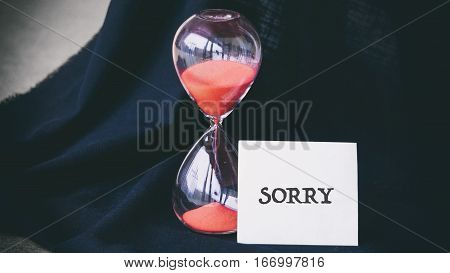 Hourglass On A Black Background, The Words On The White Sticker