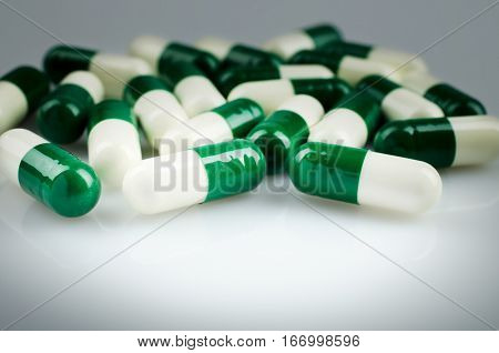 Closeup. Pharmacy theme. Green and white capsules on the white surface