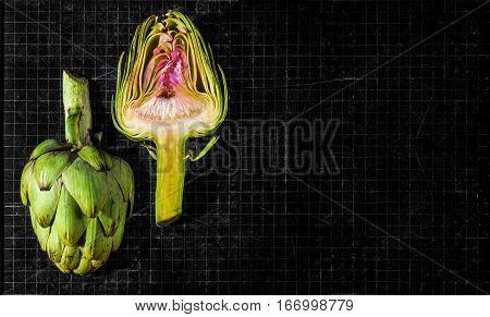 Ripe organic sliced artichokes on a antique chalkboard.