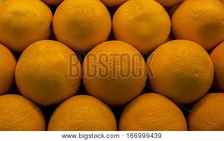 Oranges closeup photo for background. Pyramid of oranges in supermarket. Sweet vibrant exotic fruit. Tropical citrus macro photo. Oranges for sell in shop. Orange skin texture.