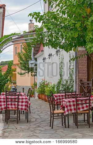 Restaurant tables on street terrace with flowers around