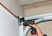 Contractor Installing Garage Door. Contractor Installing, Repair, Insulating Garage Door. Garage door seal, garage door springs, garage door replacement, garage door repair. poster