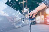 Men's hand using key unlock doors car poster