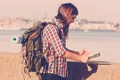 Man hiker backpacker with backpack by seaside reading map searching looking for direction guide. Adventure tourism active lifestyle. Young long haired guy tramping poster