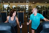 Beautiful fit senior couple in sports clothing in gym doing cardio workout, exercising on elliptical trainer machine. Sport fitness and healthy lifestyle concept. poster