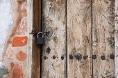 Old wooden church door with key lock and a brick wall poster