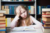 Angry and tired schoolgirl studying with a pile of books on her desk poster