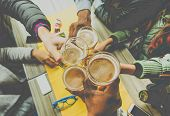 Top view of friends cheering with home brew in pub bar restaurant - Young people hands toasting and beers half pint - Friendship and party concept - Warm matte filter - Focus on bottom hand poster