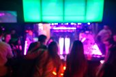 Blurred people sitting at bar counter inside disco club - Original colors lights in background - Defocused image - Concept of nightlife with music and entertainment - Warm vivid filter poster