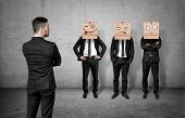 Businessman on grey concrete background turned back and looking at three men wearing carton boxes on their heads. Business communication. Corporate culture. Fitting in. poster