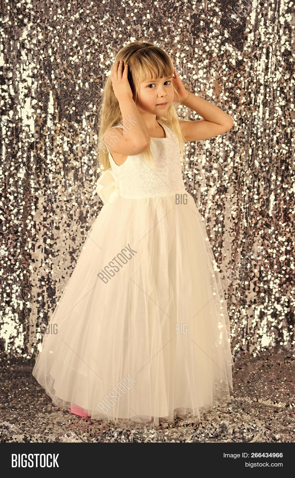 8e3fca760ba3 Look, hairdresser, makeup. Child girl in stylish glamour dress, elegance. Little  girl in fashionable dress, prom. Fashion model on silver background, ...