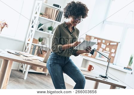 Young And Full Of Ideas. Attractive Young African Woman Using Digital Tablet And Smiling While Worki