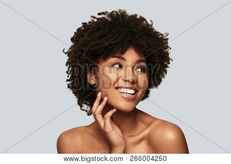 Happy Female. Attractive Young African Woman Looking Away And Smiling While Standing Against Grey Ba