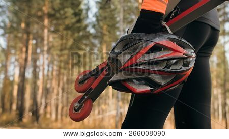 Training An Athlete On The Roller Skaters. Biathlon Ride On The Roller Skis With Ski Poles, In The H