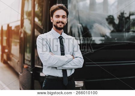 Young Smiling Businessman Standing In Front Of Bus. Confident Attractive Man Wearing White Shirt And