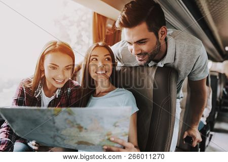 Group Of Young Smiling People Holding Paper Map. Casualy Dressed Happy Travelers Planning Route Toge