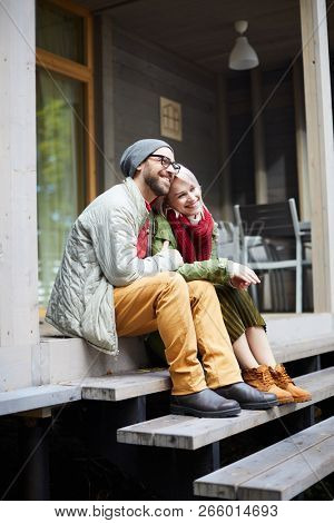 Young attractive fashionable Caucasian couple sitting on wooden steps of new house, embracing each other and smiling cheerfully