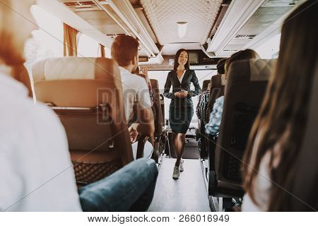 Female Tour Service Employee At Work On Tour Bus. Young Smiling Woman Standing Between Passenger Sea