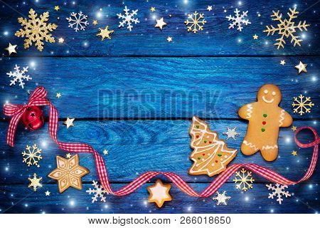 Gingerbread With Christmas Ornament On Blue Wooden Table