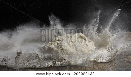 Studio Close-up Photo Of A Ball Of Bread Dough Falling On Flour