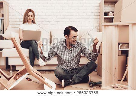 Assemble Furniture. Man Repairing Chair. Man With Furniture Instructions. Furniture Assembler With D