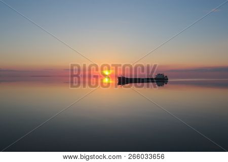 Barge Is On The Lake At Sunset. The Sun Is Reflected In The Still Water Of The Lake