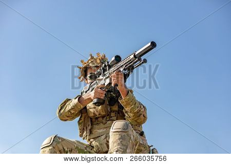 special forces, soldier assault rifle with silencer, optical sight. behind cover waiting in ambush poster