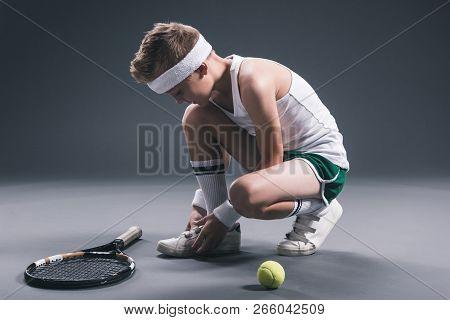 Preteen Boy In Sportswear With Tennis Racket And Ball On Dark Background