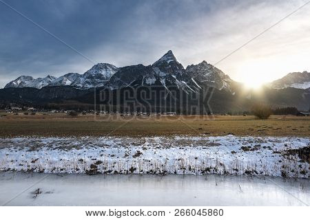 Frozen River Crossing A  Meadow With Dried Grass, A Village And The Snow-capped Alps Mountains At Su
