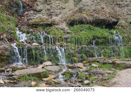Multi-tiered cascade of clean cold transparent mountain stream on the mountainside. poster