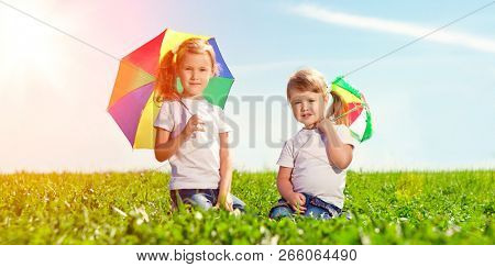 Two little girls together in outdoor park  at sunny day. Sisters in the green garden.