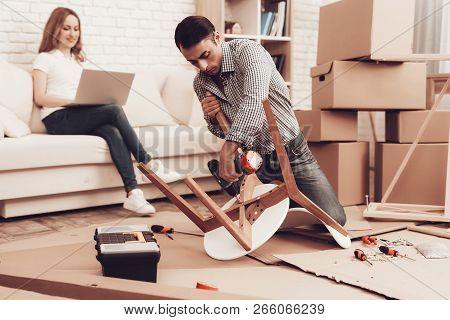 Assemble Furniture. Man Repairing Chair. Man Collects Chair. Furniture Assembler Doing New Furniture