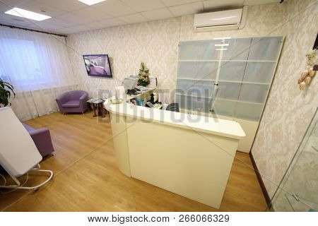Empty white reception and rest room with sofas, tv in medical center