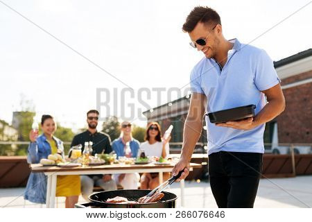 leisure and people concept - happy man with tray cooking meat on bbq and friends at rooftop party