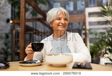 old age, leisure, retirement and people concept - happy senior woman drinking coffee at street cafe