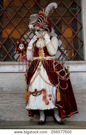 Carnival Red-white Mask And Costume At The Traditional Festival In Venice, Italy
