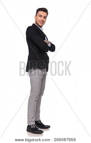confident businessman in black suit smiling and waiting in line while standing on white background with arms folded, full length picture