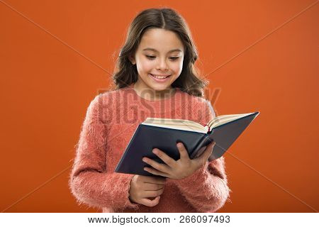 Useful Information For Her. Girl Hold Book Read Story Over Orange Background. Child Enjoy Reading Bo