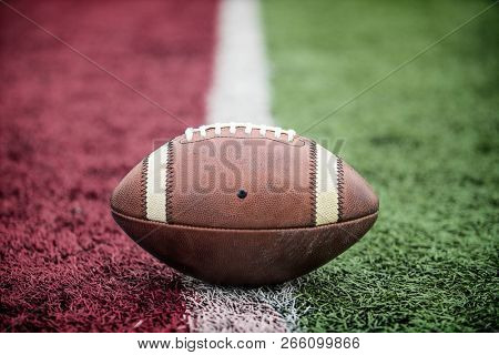 Closeup of an American Football resting on the goal line at a football stadium. Looks like its a touchdown.