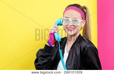 Woman In 1980s Fashion With Old Fashioned Phone On A Split Yellow And Pink Background